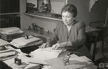 Helen Keller sitting at her desk.