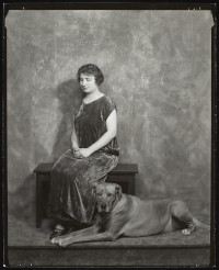 Photograph of Helen Keller seated on a bench indoors with a large dog seated beside her.; circa 1925