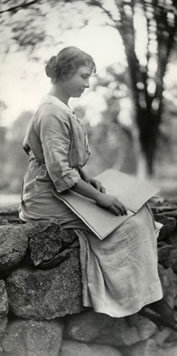 Helen sitting on a stone wall reading braille, 1902