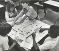 Visually impaired students playing an accessible version of Monopoly, in a classroom setting