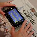 Handheld video magnifier being used to read newspaper