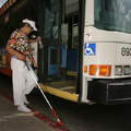 Lady with white cane boards bus