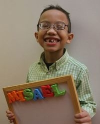 Young boy holds a magnetic board with his name
