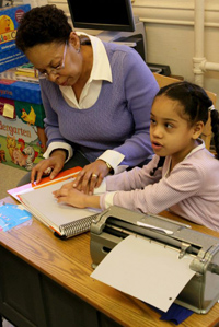 A young girl reads braille with her teacher's help