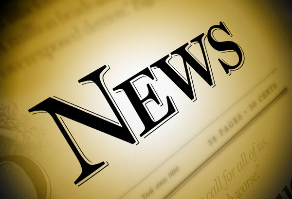 Close-up of a newspaper with the word 'News' emphasized in black on a brown/gold background.