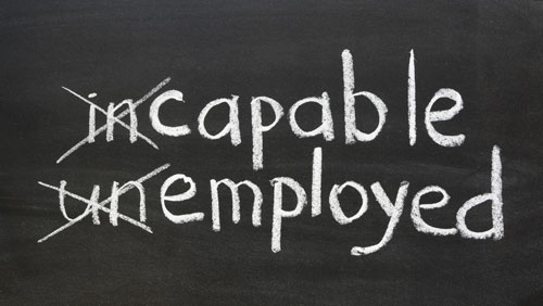The words 'incapable' and 'unemployed' on a chalkboard, with 'in' and 'un' crossed out to spell 'capable' and 'employed.'