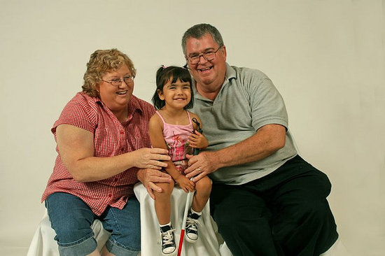 Little girl holding her white cane, sitting with her parents.
