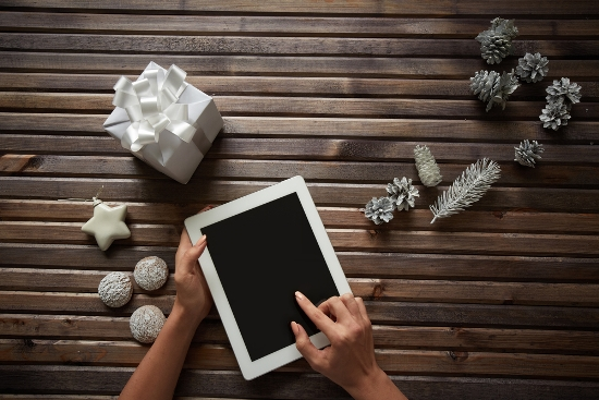 Three spice-cakes, decorative silver cones, giftbox and white toy star surrounding female hands touching display of digital tablet .