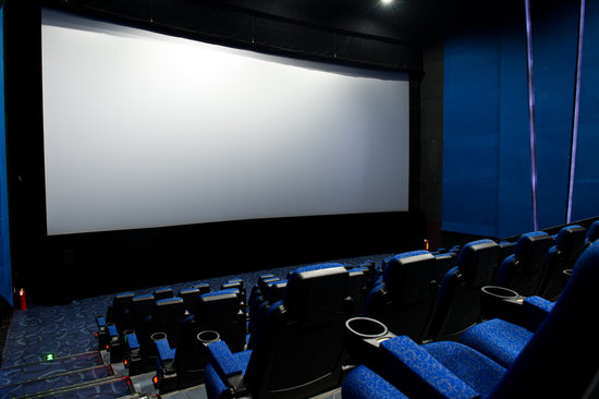 Dark movie theatre interior, screen and chairs.