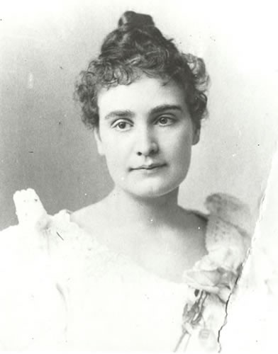 Head and shoulders portrait of Anne Sullivan, circa 1894. In this image, Anne faces the camera with a slight smile. Her head is tilted a little to her right. A long thick braid of hair appears to be curled at the top of her head and curly wisps of hair frame her face. Her light-colored dress has a wide neck with lace edging. A rose is pinned to her gown.