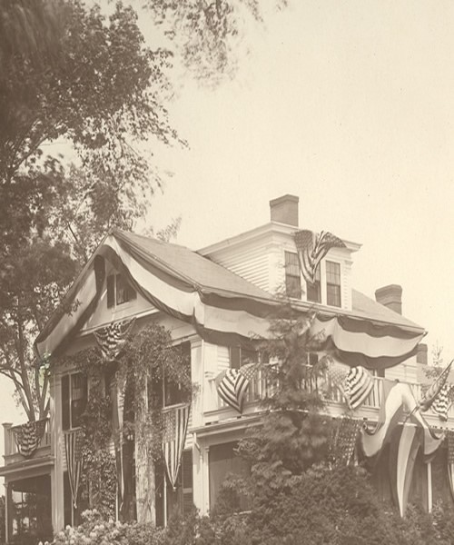 Photograph of the exterior of their three-story home in Wrentham, Massachusetts, circa 1910. The balconies on either side of the house, as well as the facade and gable, are draped with decorative material and American flags.