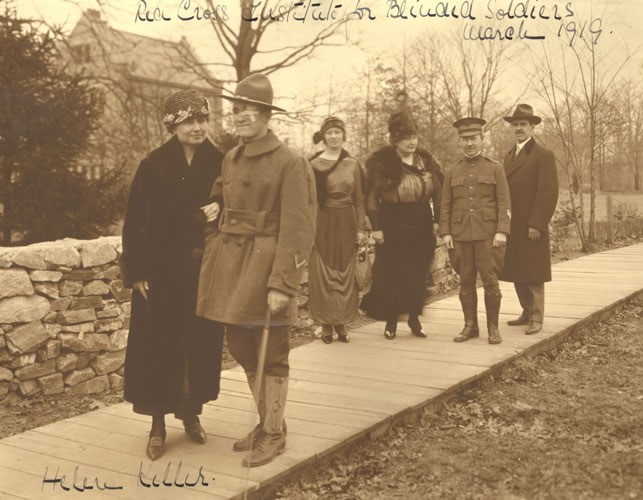 Anne, Helen, and Polly visit Evergreen, the Red Cross Institute for Blinded Soldiers in Baltimore, Maryland, March 1919. This picture shows Helen walking with a blinded soldier, her arm linked with his. Polly and Anne follow behind with a Red Cross official in uniform and another man in civilian clothes.