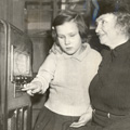 Helen Keller and a young girl sitting in front of a large cabinet radio