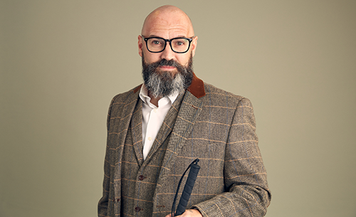 Dave Steele, wearing a gray suit with a white shirt and no tie. His head is shaved and he has a salt-and-pepper beard. He is wearing dark-framed glasses and holding a white cane.