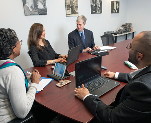 Sitting around a conference table is a group of mentors and mentees.
