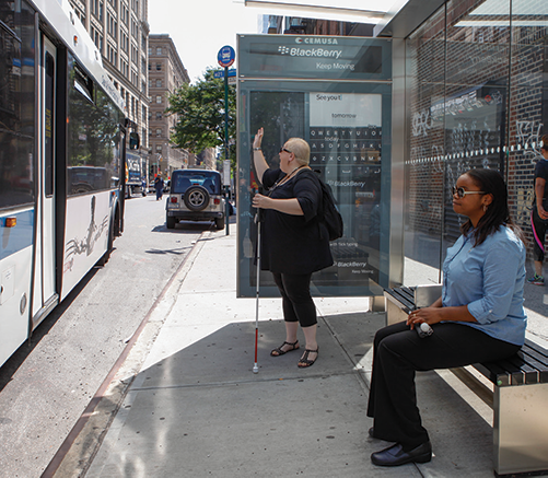 Two women waiting at a bus stop. One woman is sitting. The other is standing and hailing the public transit bus is it pulls into the stop.