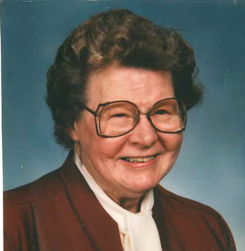 Head shot of Ruth Stank. She is middle-aged and has glasses. She is wearing a rust-colored jacket over a white blouse.