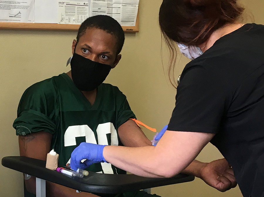 A Black man wearing a mask has blood taken for a medical test.