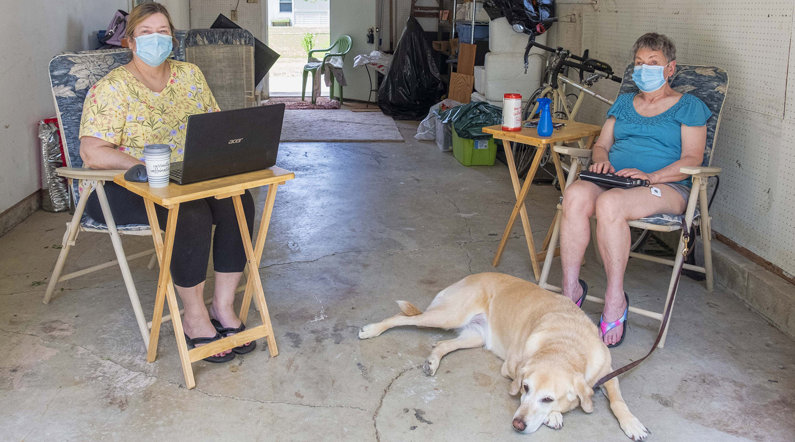 Two White women are socially distanced in a garage, both wearing masks -- one woman uses a braille notetaker as a dog lies at her feet and the other uses a laptop.