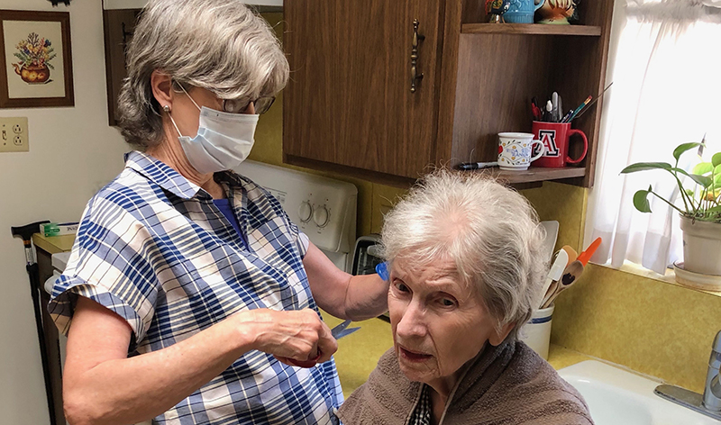 A middle-aged White woman wearing a mask cuts an older White woman's hair at home.