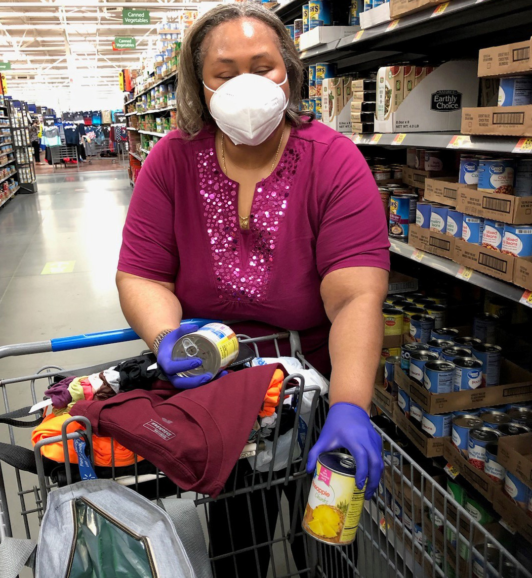 A middle-aged Black woman wearing a mask and nitrile gloves shops for groceries. She is placing a can in a shopping cart.
