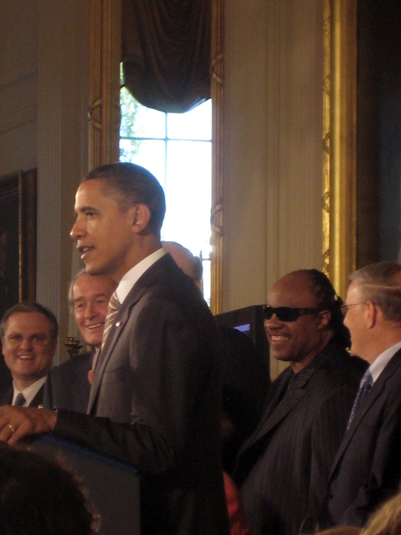 President Obama speaks at the White House during the signing of the CVAA in 2010. Stevie Wonder, Ed Markey, and others gather behind him at the podium.
