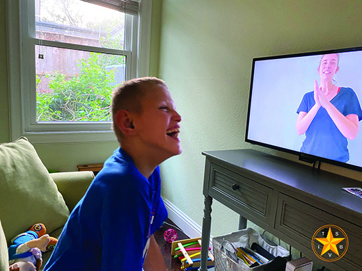 A White deafblind school-age teenager sits in front of a monitor, laughing at the image of his teacher on the screen during a Zoom lesson (courtesy TSBVI).