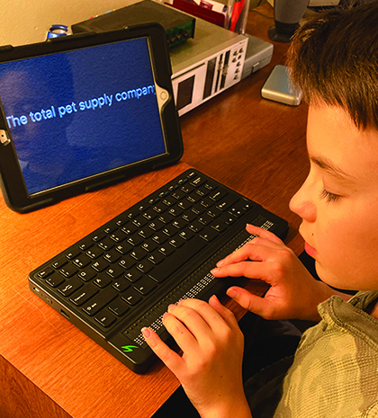 A White school-age boy uses a braille notetaker with an iPad displaying large print.
