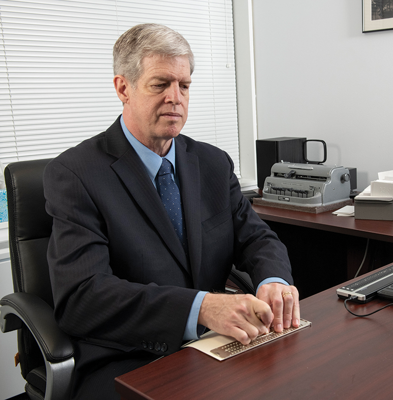 Kirk Adams sits at his desk with a braille display
