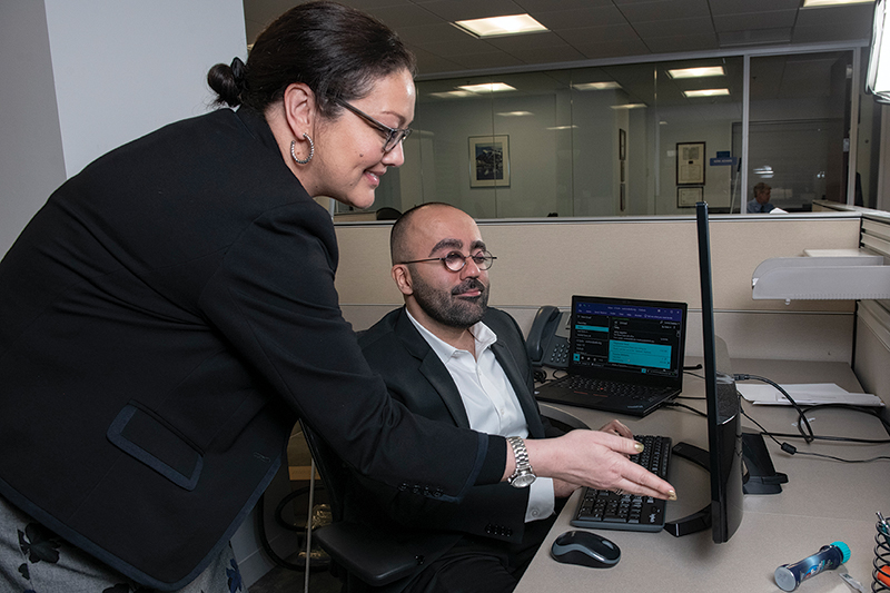 A White woman smiles as she looks at a screen with a Middle Eastern man with glasses who is seated at his desk.