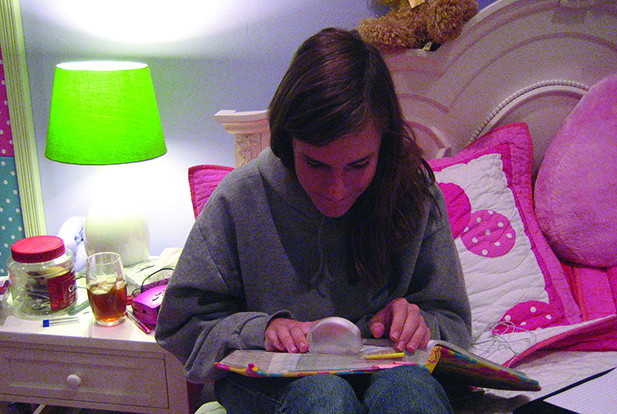 A White school-age teenager sits on a bed reading a book using a dome magnifier.