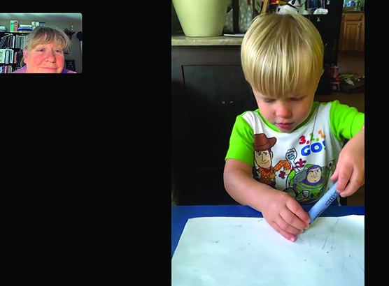 A white toddler colors with a blue crayon as a White TVI watches remotely.