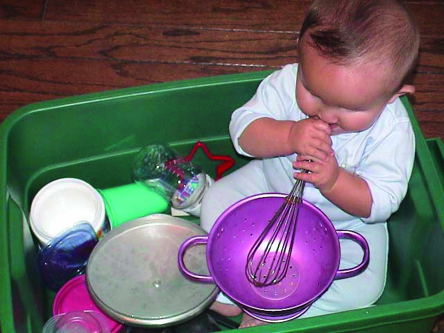 A White infant boy with additional disabilities sits in a plastic tub full of kitchen supplies. He has the end of a whisk in his mouth as he places it in a metal colander.