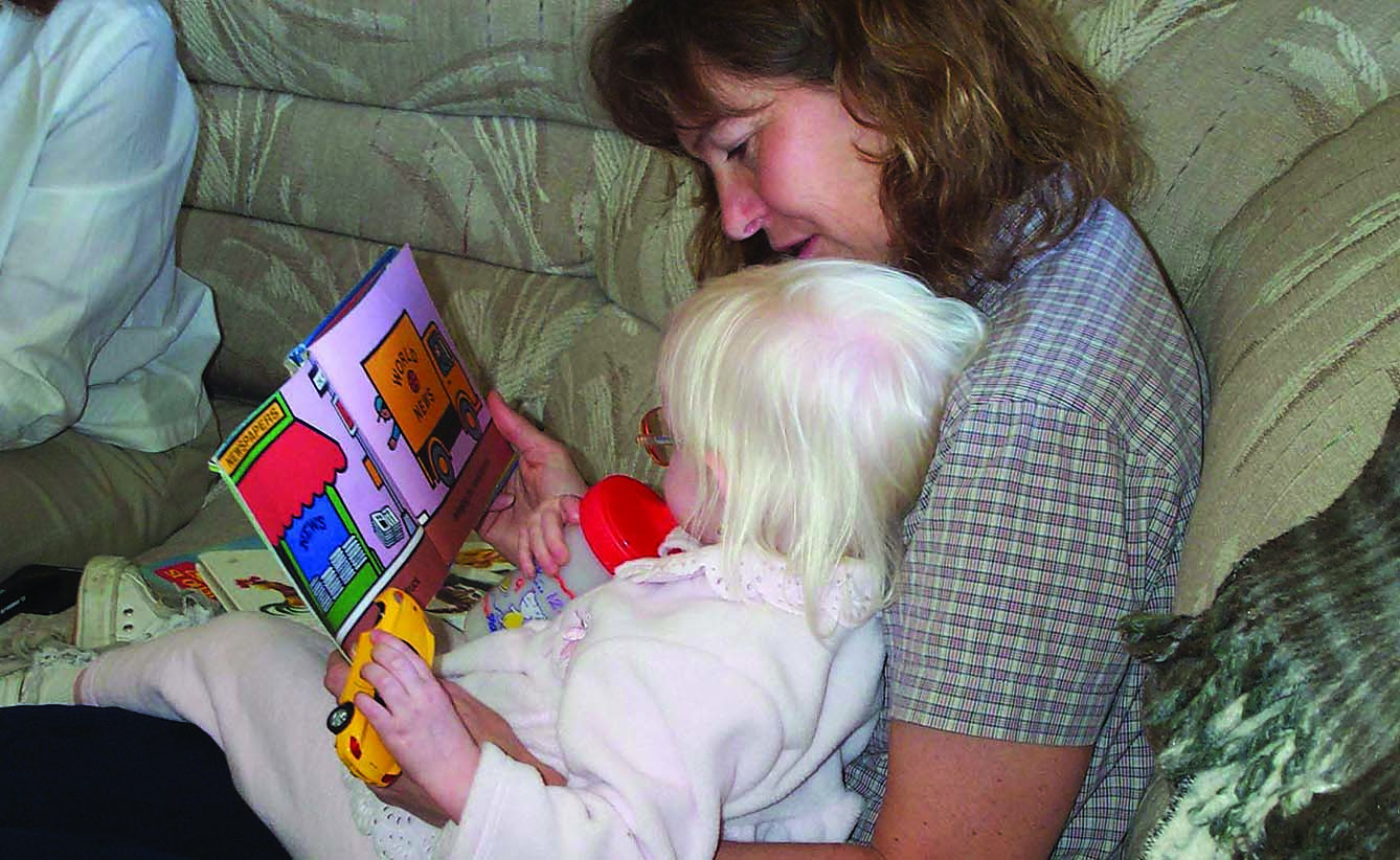 A White mother and her toddler girl with albinism explore a book together about vehicles. The toddler holds a yellow plastic car in her left hand.