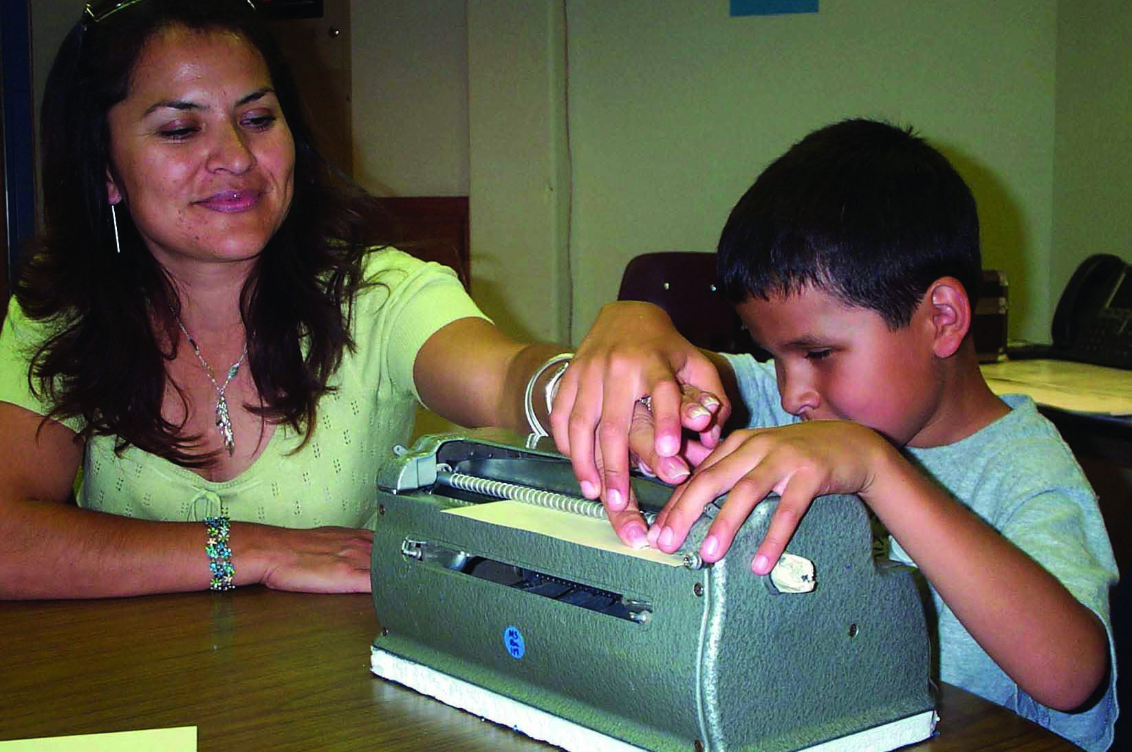 A Hispanic school-age boy takes his mother's hand to show her what he has brailled on his Perkins braillewriter.