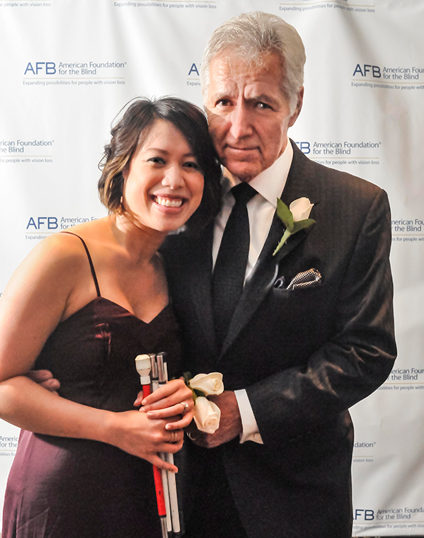 Alex Trebek stands next to Christine Ha. His right arm is around her waist and his left hand holds hers in front of them. Christine has her white can folded up and in her hands. Alex is wearing a grey suit and tie. Christine is wearing a burgundy dress with spaghetti straps.