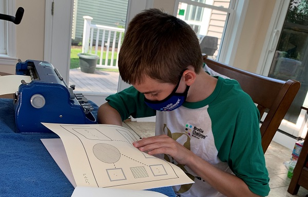 Boy sits at table next to braille embosser. He is looking through tactile graphs. He wears a mask to avoid spreading viruses.