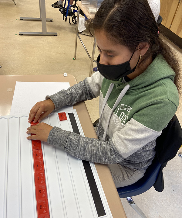 Young female student at her desk, wearing a mask, working with braille.