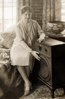 Photo of Helen Keller touching the front of a radio