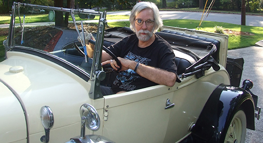 man wearing a Walters 2.8x telescope lens system to drive a replica of an antique car.