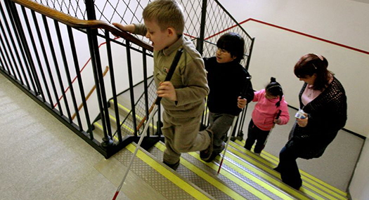 three young children using white canes to go up a school stairway, trailed by an orientation and mobility instructor