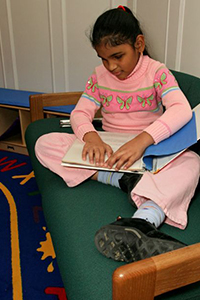 school-aged girl reading braille