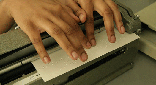Closeup of student's hands checking the braille she is embossing