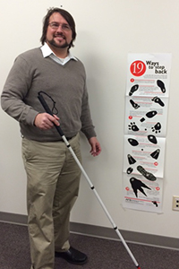 Joe Strechay with white cane in hand, posing by the 19 Ways to Step Back poster