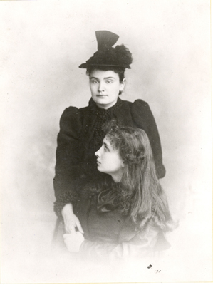 Helen Keller and Anne Sullivan Macy formal portrait. Keller is seated infront of Macy. With her left hand, Keller holds her teacher's right hand, circa 1893