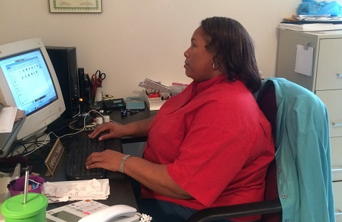 A woman in a red blouse typing on computer