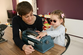 Child being taught how to use a braille writer