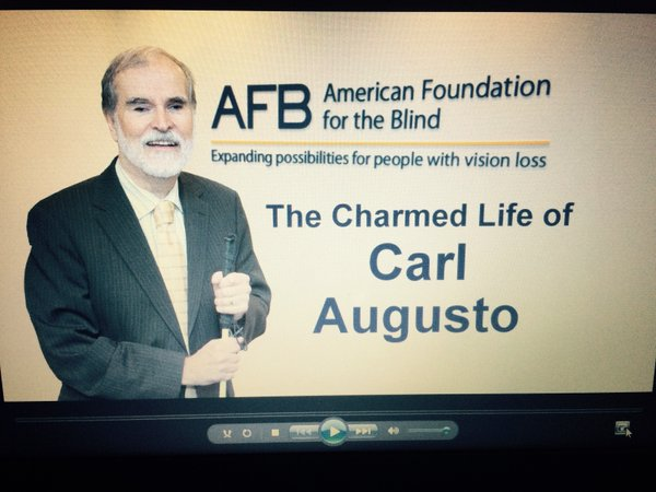 still image from the video honoring The Charmed Life of Carl Augusto - showing Carl, cane in hand, in front of the American Foundation for the Blind logo
