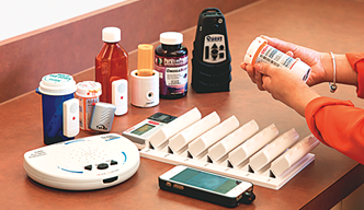 A woman holding a cell phone in her hand. A variety of medications are on a table in front of her.