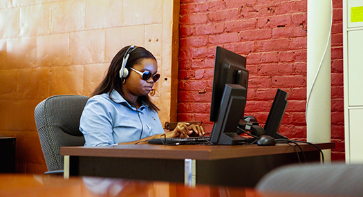 woman sitting at work desk, wearing sunglasses and using computer with headphones